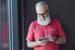 Ο εύθυμος γενειοφόρος ηληκιωμένος κρατά το smartphone με το χαμόγελο Στοκ Εικόνα