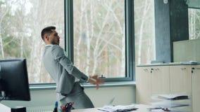 Ο εύθυμος γενειοφόρος τύπος στο μοντέρνο κοστούμι είναι χορεύοντας στην αρχή μετρητά έπειτα ρίψης στον αέρα απολαμβάνοντας την τύ απόθεμα βίντεο