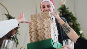 Ο εύθυμος ευτυχής τύπος στο καπέλο Άγιου Βασίλη κρατά τα μέρη των κιβωτίων δώρων για τους αγαπητούς φίλους και τη φίλη του στη Πα απόθεμα βίντεο