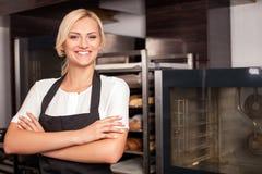 Ο εύθυμος νέος θηλυκός μάγειρας εργάζεται στο αρτοποιείο Στοκ εικόνες με δικαίωμα ελεύθερης χρήσης