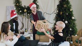 Ο εύθυμος νέος τύπος στο καπέλο Άγιου Βασίλη είναι παρουσιάζει τα κιβώτια δώρων για τους αγαπητούς φίλους και τη φίλη του στη Παρ απόθεμα βίντεο
