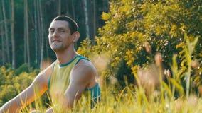 Ο εύθυμος νεαρός άνδρας κάθεται σε μια πράσινη χλόη το καλοκαίρι και χαμογελά απόθεμα βίντεο