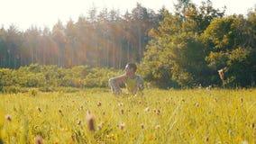 Ο εύθυμος νεαρός άνδρας κάθεται σε μια πράσινη χλόη το καλοκαίρι και χαμογελά φιλμ μικρού μήκους