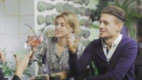 Ο εύθυμος νεαρός άνδρας και οι στενοί φίλοι γυναικών μιλούν ενώ έχοντας το μεσημεριανό γεύμα στον καφέ φιλμ μικρού μήκους