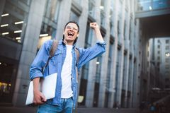 Ο εύθυμος νεαρός άνδρας με την απόλαυση σακιδίων πλάτης περπατά την πόλη με το lap-top και τη θραύση πίσω στοκ εικόνες