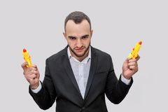 Ο εύθυμος νεαρός άνδρας στη στάση κοστουμιών και κοιτάζει στη κάμερα Θέτει Ο τύπος κρατά δύο κίτρινα πιστόλια νερού Είναι 0 απομο στοκ φωτογραφίες