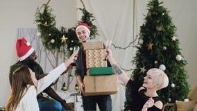 Ο εύθυμος νεαρός άνδρας στο καπέλο Άγιου Βασίλη δίνει παρουσιάζει τα δώρα στους φίλους που κάθονται στον καναπέ και το κρασί κατα απόθεμα βίντεο