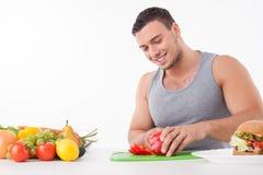 Ο εύθυμος νεαρός άνδρας προτιμά να μαγειρεψει τα υγιή τρόφιμα Στοκ Φωτογραφίες