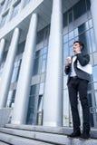 Ο εύθυμος νεαρός άνδρας στο κοστούμι εργάζεται υπαίθρια Στοκ εικόνα με δικαίωμα ελεύθερης χρήσης