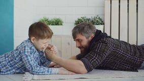 Ο εύθυμος πατέρας διδάσκει ο μικρός βραχίονας γιων ότι του που παλεύει, που παρουσιάζει του θέση χεριών και που για να χάσει, αγό απόθεμα βίντεο