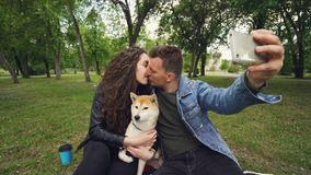 Ο εύθυμος τύπος παίρνει selfie το smartphone εκμετάλλευσης και φιλά τη σύζυγό του ενώ κρατά το λατρευτό σκυλί και το φιλά φιλμ μικρού μήκους