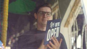 Ο εύθυμος υπάλληλος καφέδων στην ποδιά αλλάζει doorplate από ` θλιβερό εμείς είναι κλειστό ` σε ` ναι εμείς είναι ανοικτό ` Αρχικ απόθεμα βίντεο