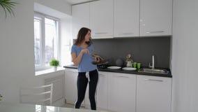 Ο εύθυμος χορός οικονόμων και τραγουδά με το τηγάνι και τα πιάτα στα χέρια μαγειρεύοντας το γεύμα στην κουζίνα στο σπίτι στις δια απόθεμα βίντεο