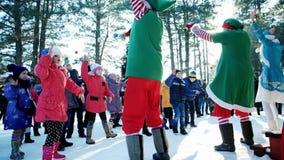 Ο εύθυμος χορός στο χιόνι σε ένα πάρκο στο νέο φεστιβάλ έτους, εμψυχωτές παίζει με τα παιδιά, εορτασμοί Χριστουγέννων μέσα φιλμ μικρού μήκους