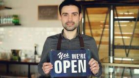 Ο εύθυμος όμορφος ιδιοκτήτης καφέ ατόμων μικρός κρατά ` που είμαστε ανοικτό σημάδι ` στεμένος μέσα στη καφετερία άνοιγμα απόθεμα βίντεο