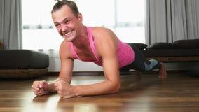 Ο εύθυμος όμορφος τύπος σε μια ρόδινη μπλούζα συμμετείχε στην ικανότητα, στο καθιστικό του σπιτιού του απόθεμα βίντεο