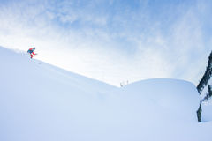 Ο ελεύθερος σκιέρ κατεβαίνει από το βουνό λαμβάνοντας υπόψη το μ Στοκ Φωτογραφία