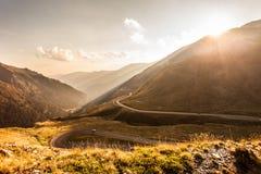 Ο ελικοειδής δρόμος μέσω των ηλιοφώτιστων βουνών Στοκ Φωτογραφίες