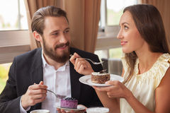 Ο ελκυστικοί άνδρας και η γυναίκα δοκιμάζουν τα γλυκά τρόφιμα μέσα Στοκ Εικόνες