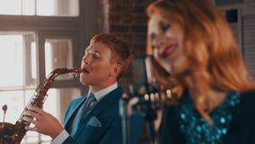 Ο ελκυστικός αοιδός τζαζ αποδίδει στη σκηνή με το saxophonist στο μπλε κοστούμι μουσική απόθεμα βίντεο