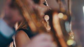 Ο ελκυστικός αοιδός τζαζ με φωτεινό αποτελεί να αποδώσει στη σκηνή με το saxophonist απόθεμα βίντεο