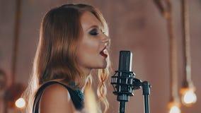 Ο ελκυστικός αοιδός τζαζ με φωτεινό αποτελεί την απόδοση στη σκηνή στο μικρόφωνο απόθεμα βίντεο