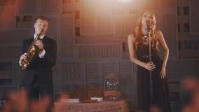 Ο ελκυστικός αοιδός τζαζ στο μαύρο φόρεμα αποδίδει στη σκηνή με το χορό saxophonist απόθεμα βίντεο