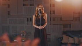 Ο ελκυστικός αοιδός τζαζ στο μαύρο φόρεμα αποδίδει στη σκηνή στο μικρόφωνο χορός φιλμ μικρού μήκους