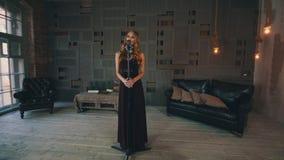 Ο ελκυστικός αοιδός τζαζ στο μαύρο φόρεμα αποδίδει στη σκηνή στο μικρόφωνο συναυλίας φιλμ μικρού μήκους