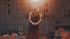 Ο ελκυστικός αοιδός τζαζ στο μαύρο φόρεμα αποδίδει στη σκηνή στο μικρόφωνο η γυναίκα με το ραβδί φιλμ μικρού μήκους