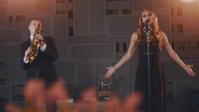 Ο ελκυστικός αοιδός τζαζ στο μαύρο φόρεμα εκτελεί το χορό στη σκηνή με το saxophonist απόθεμα βίντεο