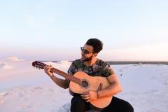 Ο ελκυστικός αραβικός τύπος τραγουδά τα τραγούδια στην κιθάρα, καθμένος στο λόφο μέσα Στοκ φωτογραφία με δικαίωμα ελεύθερης χρήσης