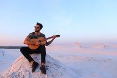 Ο ελκυστικός αραβικός τύπος τραγουδά τα τραγούδια στην κιθάρα, καθμένος στο λόφο μέσα Στοκ Φωτογραφίες