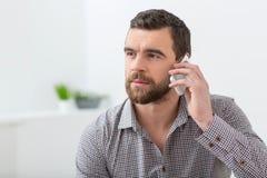 Ο ελκυστικός γενειοφόρος τύπος επικοινωνεί σε ένα τηλέφωνο Στοκ Φωτογραφία