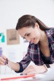 Ο ελκυστικός θηλυκός σχεδιαστής εργάζεται σε ένα σχεδιάγραμμα στοκ εικόνες