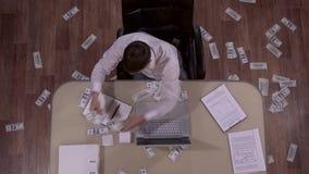 Ο ελκυστικός νέος επιχειρηματίας που παίρνει τα χρήματα από τον πίνακα και τους ρίχνει γύρω από τον απόθεμα βίντεο