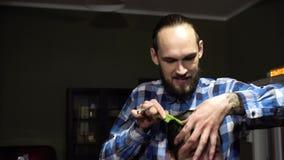 Ο ελκυστικός νέος κουρέας είναι τέμνοντα ανθρώπινα μαλλιά με το ψαλίδι Εξετάζει την τρίχα με τη συγκέντρωση Ο γενειοφόρος απόθεμα βίντεο