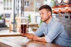 Ο ελκυστικός νέος μπάρμαν περιμένει τους πελάτες Στοκ Φωτογραφίες