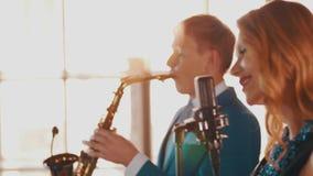 Ο ελκυστικός χορός αοιδών τζαζ τραγουδά στη σκηνή με το saxophonist στο μπλε κοστούμι απόθεμα βίντεο