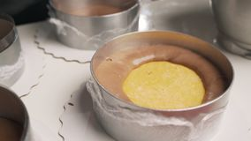 Ο ζαχαροπλάστης γυναικών μαύρο σε ομοιόμορφο προετοιμάζει την κρέμα για mousse σοκολάτας το κέικ Σκηνικό μαγειρεύοντας mousse κέι φιλμ μικρού μήκους