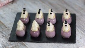 Ο ζαχαροπλάστης διακοσμεί mousse το κέικ με μια παραγωγή βακκινίων των βερνικωμένων επιδορπίων απόθεμα βίντεο