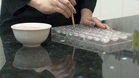Ο ζαχαροπλάστης εφαρμόζει τη γλυκιά κόλλα στο κατώτατο σημείο της μορφής ψησίματος για τις καραμέλες, κλείνει επάνω φιλμ μικρού μήκους