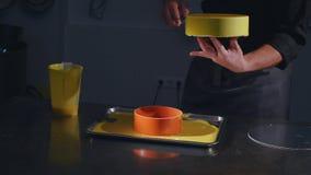 Ο ζαχαροπλάστης με spatula διέδωσε το λούστρο σε ένα πρόσφατα ψημένο κέικ σε μια επαγγελματική κουζίνα σε ένα αρτοποιείο Κύπελλο  απόθεμα βίντεο