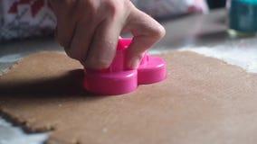 Ο ζαχαροπλάστης πιέζει την πλαστική φόρμα με μορφή μιας καρδιάς και αποκόπτει τα μπισκότα απόθεμα βίντεο