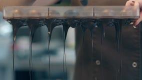 Ο ζαχαροπλάστης τρυπά τη σκοτεινή σοκολάτα από το μαγείρεμα της μορφής με διατρητική μηχανή φιλμ μικρού μήκους