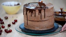 Ο ζαχαροπλάστης χύνει τη σοκολάτα στο κέικ απόθεμα βίντεο