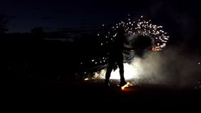 Ο ζογκλέρ αναφλέγει τη Βεγγάλη ελαφρύ Sparklers βαθιά τη νύχτα στην slo-Mo Φαίνονται μαγικοί φιλμ μικρού μήκους