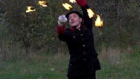 Ο ζογκλέρ περιστρέφει δύο ανεμιστήρες μετάλλων με τη φλόγα γύρω από τον στην slo-Mo Είναι μαγικό φιλμ μικρού μήκους