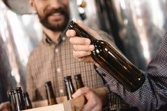 Ο ζυθοποιός κρατά το κενό μπουκάλι μπύρας διαθέσιμο Στάδια της παρασκευάζοντας παραγωγής Διαδικασία της κατασκευής μπύρας Στοκ Εικόνες