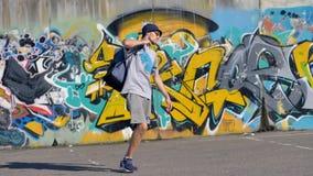 Ο ζωγράφος γκράφιτι βάζει τα βαρέλια χρωματισμού του στο σακίδιο πλάτης και περπατά μακριά φιλμ μικρού μήκους